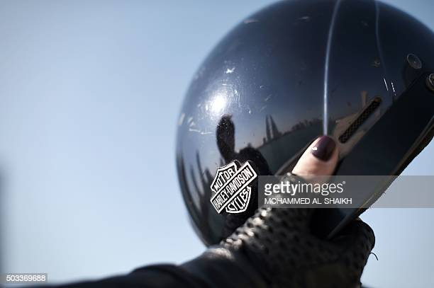 Bahraini Anne alZayani biker and head of Public Relations at the American Mission Hospital holds her helmet as she sits on her motorbike in the...