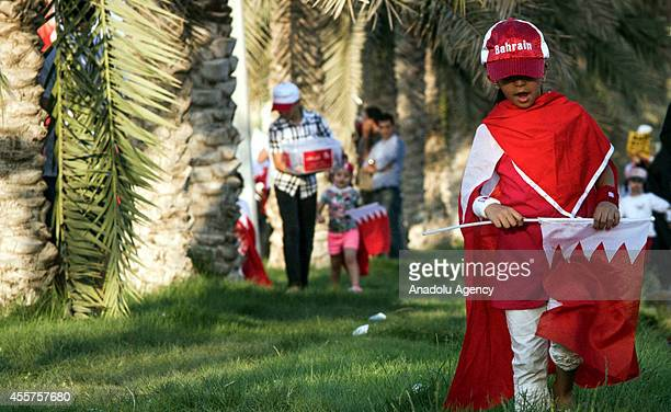 Bahraini boy holds the flag of Bahrain during a demonstration held for demanding the release of political detainees in Manama capital city of Bahrain...