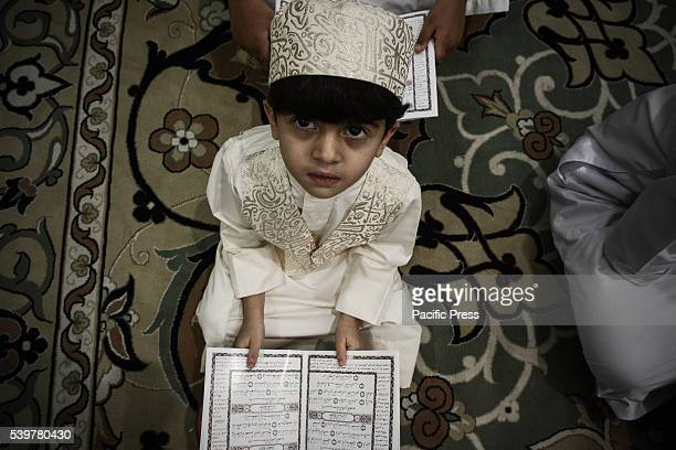 Bahraini boy is reading the Quran on the eve of Ramadan The Quran is the central religious text of Islam which Muslims believe to be a revelation...