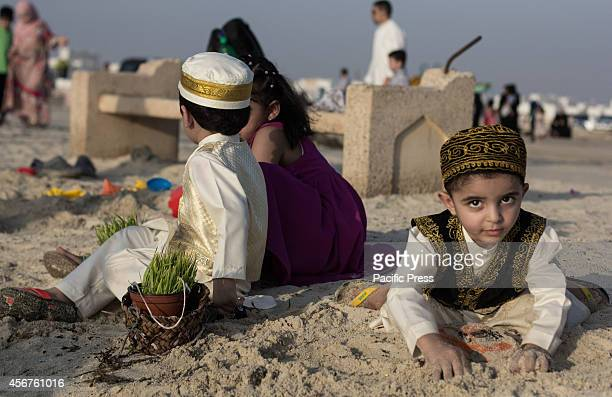 Bahraini child crawling in the sand during the throwing of barley seedlings into the water at Malkiah beach Devotees throw barley into the water at...