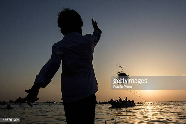 Bahraini child throws barley seedlings into the water at Malkiah beach Devotees throw barley into the water at the end of 'Eid alAdha' one of the...