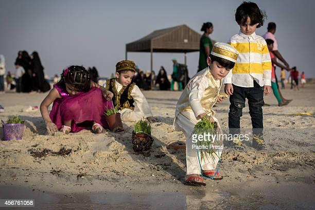 Bahraini children try to throw barley seedlings into the water at Malkiah beach Devotees throw barley into the water at the end of 'Eid alAdha' one...