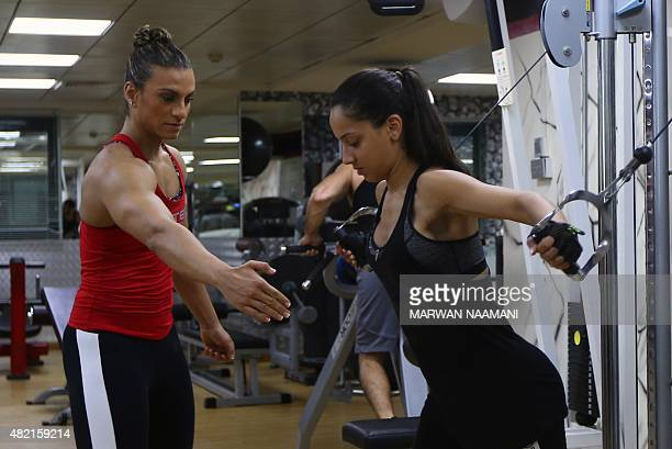 Bahraini female bodybuilder and personal trainer Haifa alMusawi trains YemeniBirtish Shaza Jamil at a gym in Dubai on June 26 2015 Proudly flexing...