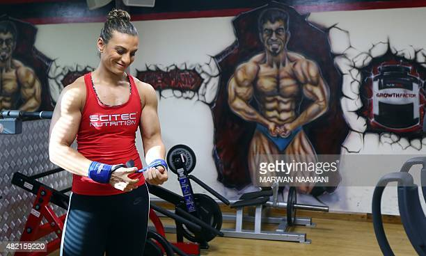 Bahraini female bodybuilder and personal trainer Haifa alMusawi prepares to train at a gym in Dubai on June 26 2015 Proudly flexing her muscles in...