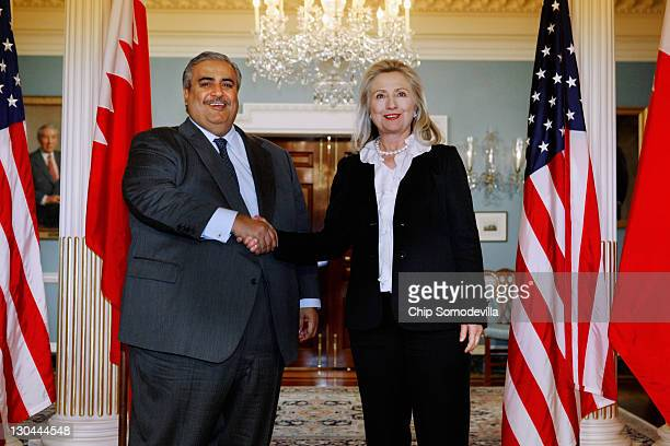 Bahraini Foreign Minister Shaikh Khalid bin Ahmed al-Khalifa poses for photographs while shaking hands with U.S. Secretary of State Hillary Clinton...