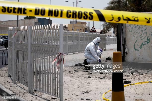 A Bahraini forensic police officer inspects the site of a bomb blast in the village of Sitra south of Manama on July 28 2015 The blast killed two...