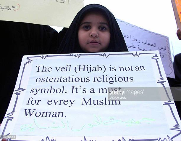 Bahraini girl holds up a banner during a demonstration close to the French Embassy in Manama 17 January 2004 against plans by the French government...