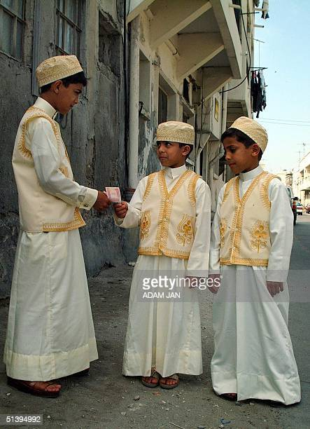Bahraini kids wearing their traditional outfit count their pocket money for the Muslim holiday of Eid alAdha in Manama 05 March 2001 The threeday...