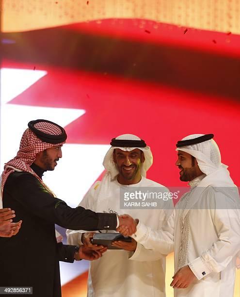 Bahraini kings son Sheikh Khaled bin Hamad bin Issa alKhalifa shakes hands with winning Bahraini poet Mohammed alArjany who came fourth among the...