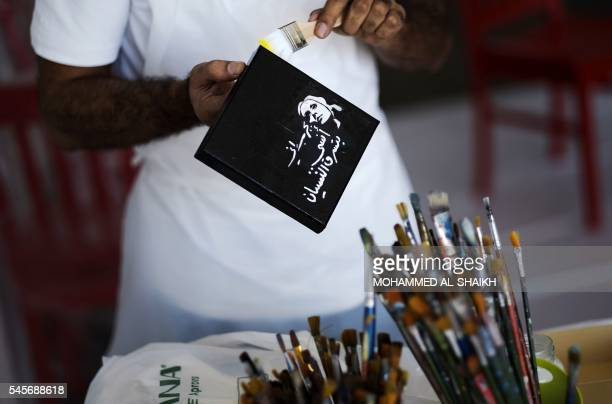A Bahraini man paints on a box bearing a portrait of Egyptian late singer and actress Fairouz during a painting event at Mashq Art Space gallery in...