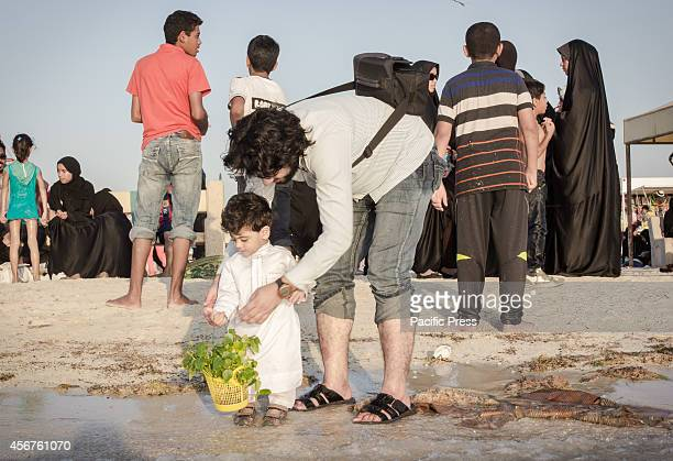 Bahraini man teaches his son to throw barley seedlings into the water at Malkiah beach Devotees throw barley into the water at the end of 'Eid...