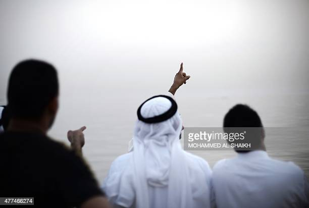 Bahraini men gather near the beach searching the sky for the crescent moon in the village of Karzakan south of Manama as the faithful prepare for the...