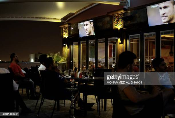 Bahraini men watch a screen at a cafe in the city of Muharraq north of capital Manama on early June 13 2014 during a live screening of a 2014 FIFA...