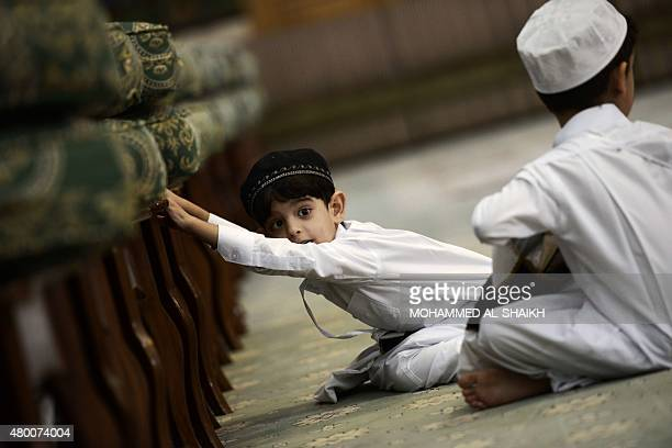 A Bahraini Muslim boy looks on during a reading of the Koran Islam's holy book during the holy fasting month of Ramadan on July 9 at a mosque in the...