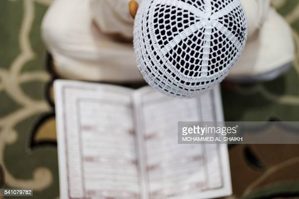 A Bahraini Muslim boy reads the Koran Islam's holy book during the holy fasting month of Ramadan at a mosque in the village of Sanabis west of Manama...