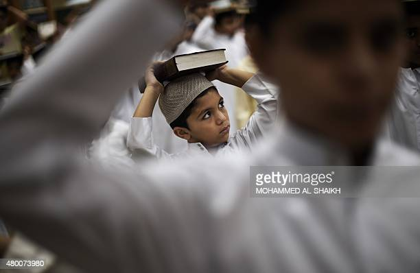 Bahraini Muslim boys attend a reading of the Koran Islam's holy book during the holy fasting month of Ramadan on July 9 at a mosque in the village of...