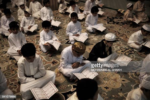 Bahraini Muslim boys read the Koran Islam's holy book during the holy fasting month of Ramadan at a mosque in the village of Sanabis west of Manama...