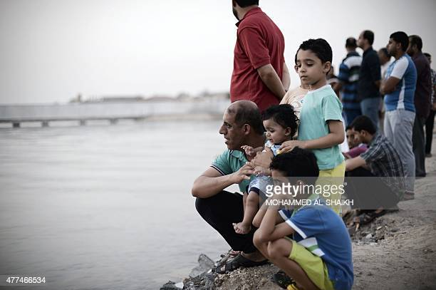 Bahraini Muslims gather near the beach searching the sky for the crescent moon in the village of Karzakan south of Manama as the faithful prepare for...