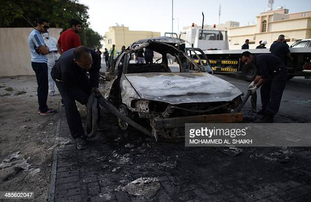 Bahraini police inspect the debris of a car at the site of an explosion in the village of Al Maqsha west of Manama on April 19 2014 Two people were...