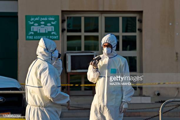 Bahraini policemen seal off a building housing foreign workers in the Salmabad industrial area as a precautionary measure after a resident tested...