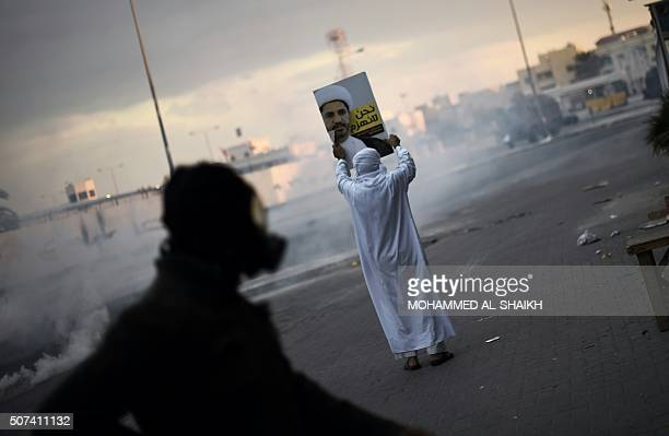Bahraini protester holds a placard depicting a portrait of Sheikh Ali Salman head of the Shiite opposition movement alWefaq during clashes with riot...