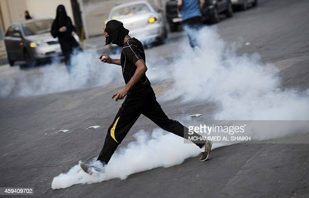 A Bahraini protester kicks a can of tear gas in clash with riot police during a demonstration against the ongoing parliamentary elections in the...