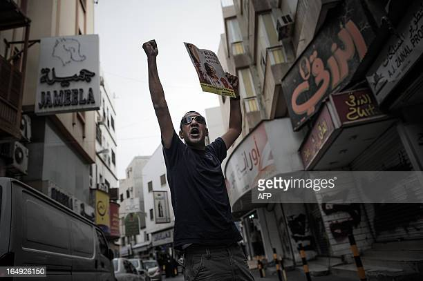 A Bahraini protester shouts slogans while holding a poster of jailed human rights activist Nabeel Rajab during an antiregime protest in solidarity...