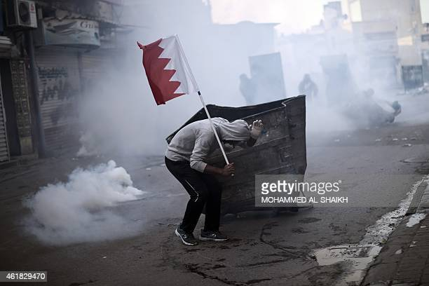 A Bahraini protester takes cover during clashes with police following a demonstration against the arrest of Sheikh Ali Salman head of the Shiite...