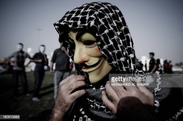 Bahraini protester wearing a Guy Fawkes mask used by the Anonymous movement takes part in a demonstration against the government and in solidarity...