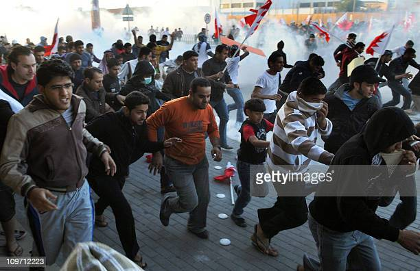 Bahraini protesters run for cover from tear gas fired by police to disperse them in the village of Sanabis near Manama on February 14 2011 during a...