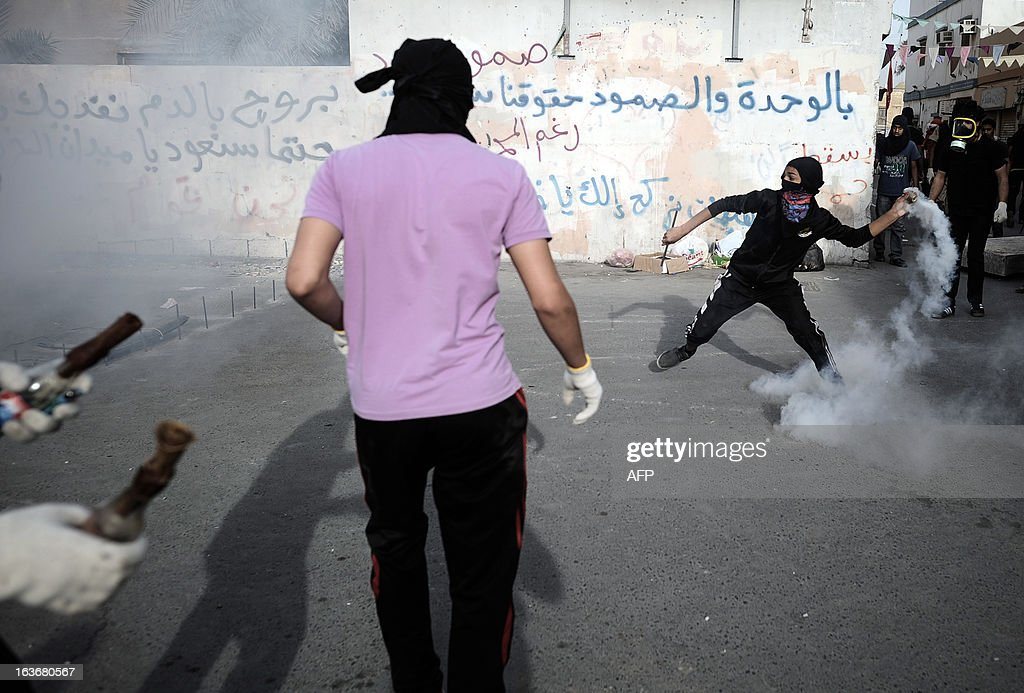 A Bahraini protestor throws a tear gas canister back towards riot police during clashes following an anti-government demonstration in the village of Sanabis, West of Manama on March 14, 2013. Bahraini police clashed with youths protesting against the deployment into a third year of a Gulf military force that backed Manama's bid to crush a Shiite-led uprising, witnesses said.