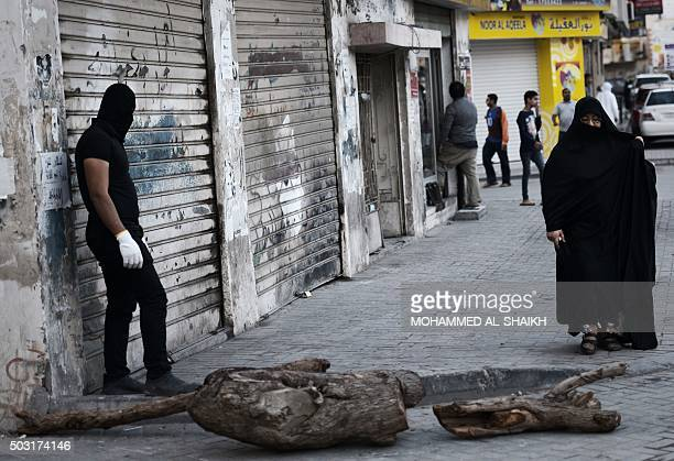 A Bahraini protestor uses a palm trunk to block a road during clashes with riot police following a protest in the village of Jidhafs west of Manama...