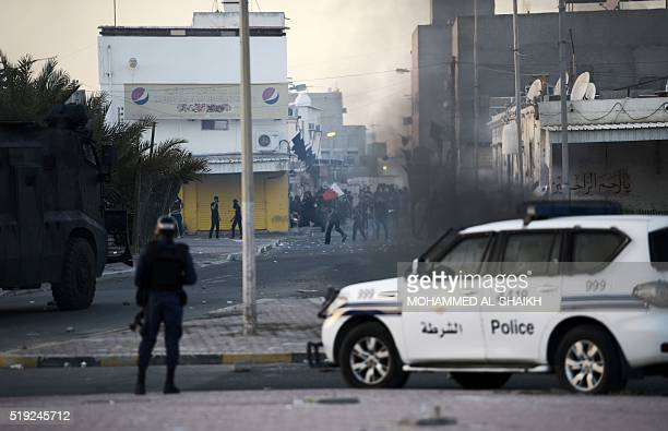 Bahraini protestors throw stones towards riot police during clashes following the funeral of Ali Abdulghani whose family says died of injuries...