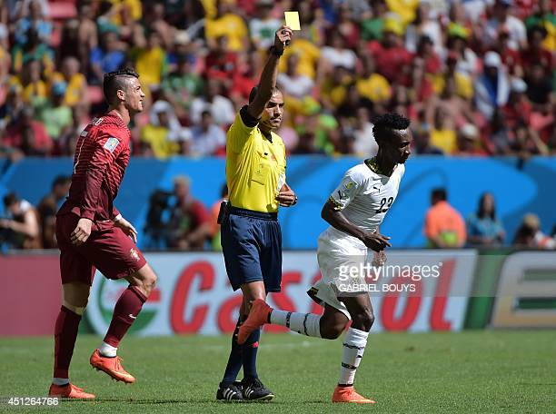 Bahraini referee Nawaf Abdulla Ghayyath Shukralla shows the yellow card to Ghana's defender Harrison Afful for fouling Portugal's forward and captain...