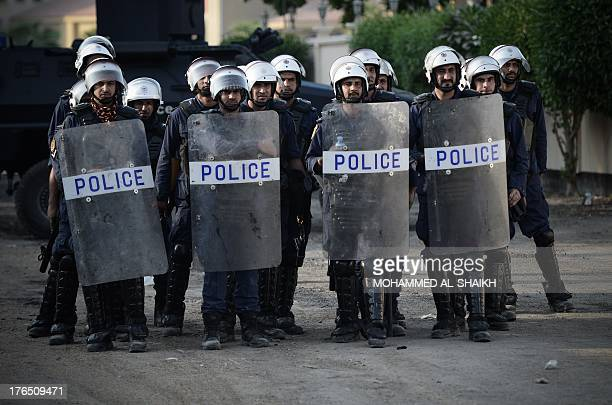 Bahraini riot police stand guard during demonstration against the ruling regime in the village of Shakhora west of Manama on August 14 2013Bahraini...