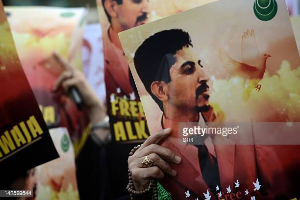 Bahraini Shiite demonstrators hold posters of jailed activist Abdulhadi al-Khawaja during a protest calling for his release in the village of...