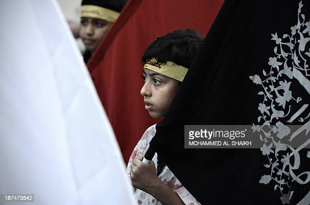 Bahraini Shiite Muslim boys take part in a ceremony marking Ashura which commemorates the seventh century slaying of Imam Hussein the grandson of...