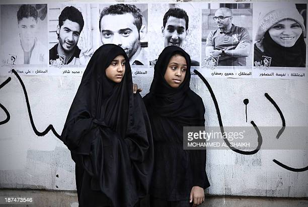 Bahraini Shiite Muslim women stand in front of a portraits of detained political activists during a ceremony marking Ashura which commemorates the...