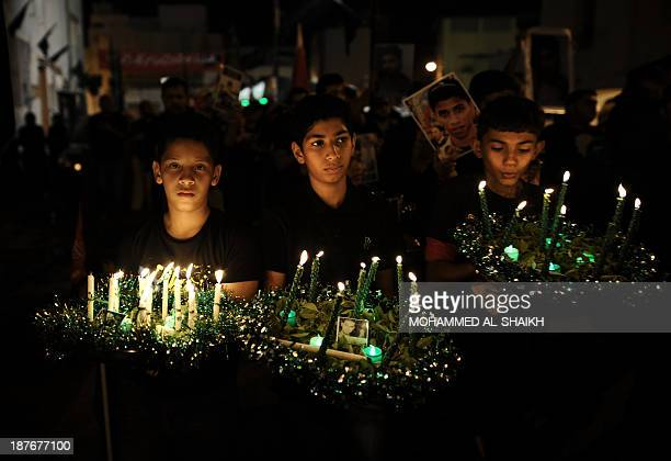 Bahraini Shiite Muslims boys carry candles during a ceremony marking Ashura which commemorates the seventh century slaying of Imam Hussein the...