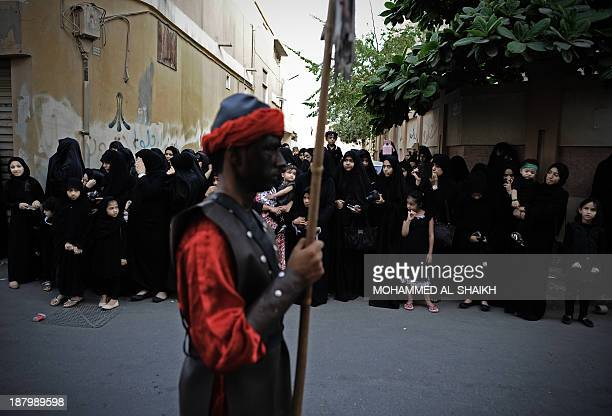 Bahraini Shiite Muslims take part in a ceremony marking Ashura which commemorates the seventh century slaying of Imam Hussein the grandson of Prophet...