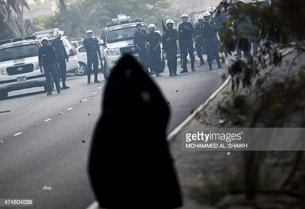 A Bahraini Shiite woman stands in front of riot policemen during clashes on May 23 2015 in the village of Jidhafs west of Manama following a protest...