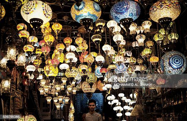 Bahraini vendor poses for the picture in his lantern shop at the old manama market in the Bahrain capital city of Manama late on June 10 2016 during...