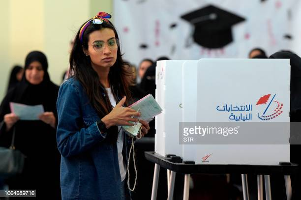 Bahraini voters cast their ballot for parliamentary election at a polling station in the Bahraini city of AlMuharraq north of Manama on November 24...