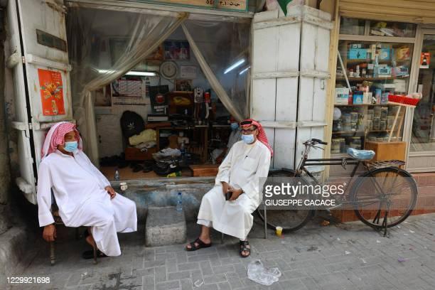 Bahraini wearing mask due to the Covid-19 pandemic, sit outside a shoe repair shop at the Suq al-Qaisariya, in Muharraq Island, in the Bahraini...
