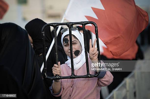 """Bahraini woman flashes the """"V"""" for victory sign during an anti-government rally in solidarity with jailed political activists in the village of..."""