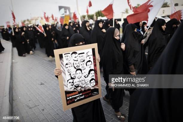 Bahraini woman holds a placard featuring portraits of jailed political activists during an anti-government protest in the village of Jannusan, west...