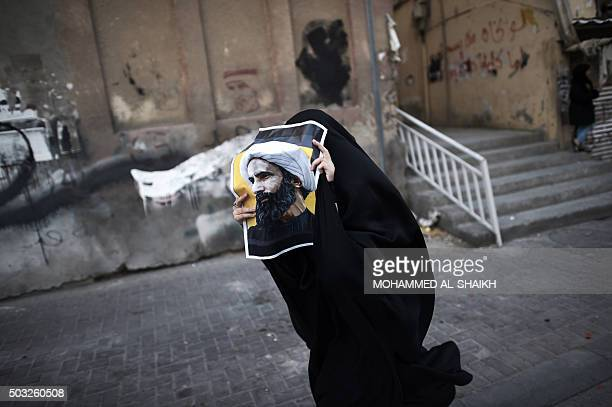 Bahraini woman holds a poster bearing a portrait of prominent Shiite Muslim cleric Nimr alNimr during a protest against his execution by Saudi...