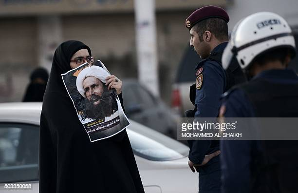 Bahraini woman holds a poster of prominent Shiite Muslim cleric Nimr alNimr during clashes with riot police following a protest against the execution...