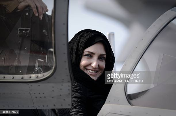 A Bahraini woman looks at an aircraft during the opening of the Bahrain International Airshow 2014 in Sakhir south of the capital Manama on January...