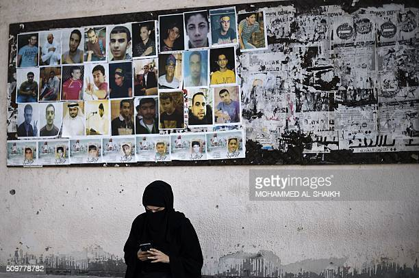 Bahraini woman sits near portraits of jailed political activists and protesters killed during clashes with police, before taking part in a...